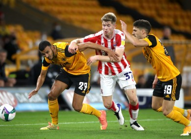Stoke City's Nathan Collins tangles with Romain Saiss and Ruben Vinagre of Wolves.