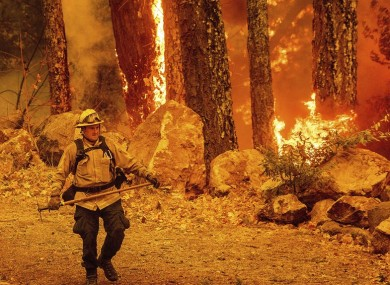 A firefighter walks a path as the Glass Fire burns along Highway 29 in Calistoga, California