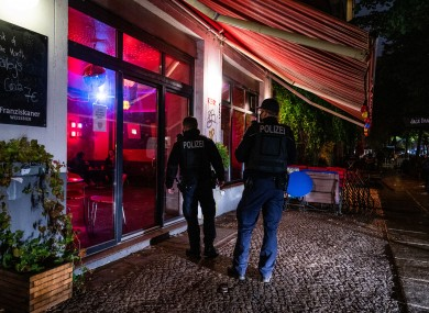 Pictured are two Berlin policemen checking that the curfew is observed in the Friedrichshain district, 14 October.