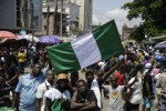 People hold banners as they demonstrate on the street to protest against police brutality, in Lagos