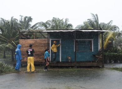 Residents stand outside a home surrounded by floodwaters brought on by Hurricane Eta in Wawa, Nicaragua