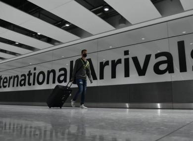 Passenger wearing face mask walking through Heathrow.
