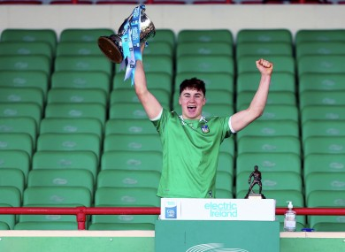 Limerick's Adam English lifts the trophy at the end of the game.