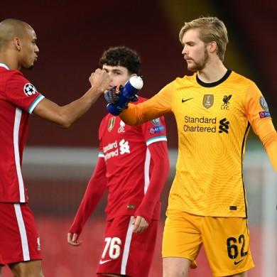 Liverpool's Fabinho (left) and goalkeeper Caoimhin Kelleher bump fists.