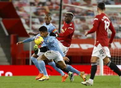 Manchester City's Fernandinho and Rodri battle with Manchester United's Paul Pogba