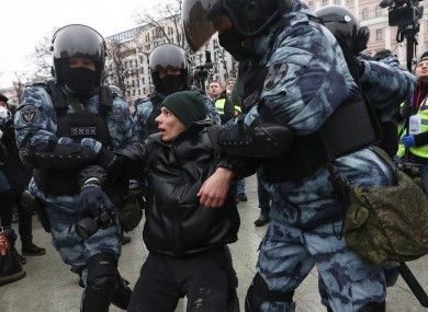 Police detain a man in Moscow during pro-Navalny protests yesterday.