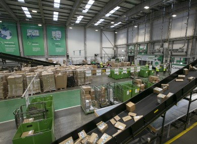 staff loading cardboard boxes on to conveyor belts for delivery at An Post's Parcel Hub in Dublin