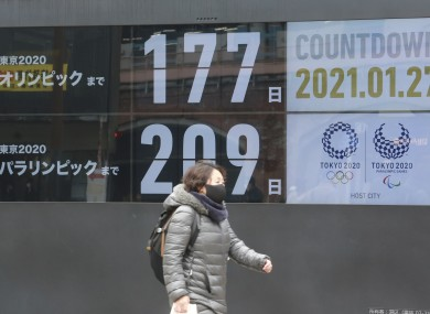 A pedestrian walks by a clock counting down to the Olympics and Paralympics in Tokyo.