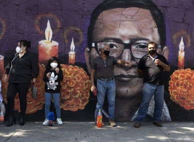 People wait in front of a mural outside the San Nicolas Tolentino cemetery in the Iztapalapa district of Mexico City.