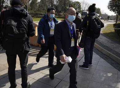 WHO researchers leaving a Wuhan hotel yesterday.