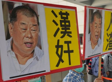 Pro-China supporters hold the pictures of Jimmy Lai with words