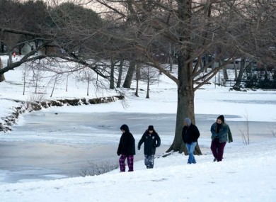 People walk along the edge looking at the frozen lake at Cottonwood Park in Richardson, Texas