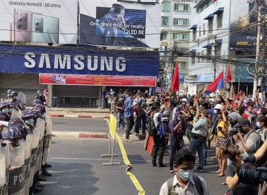 Riot police block the road to prevent protesters from marching forward in capital Yangon