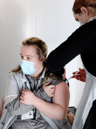 A home care assistant is vaccinated in DCU.