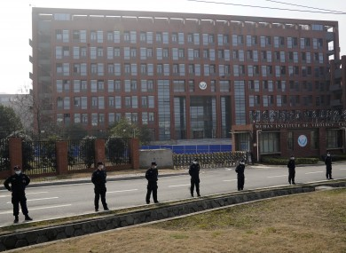 Security personnel gather near the entrance of the Wuhan Institute of Virology today.