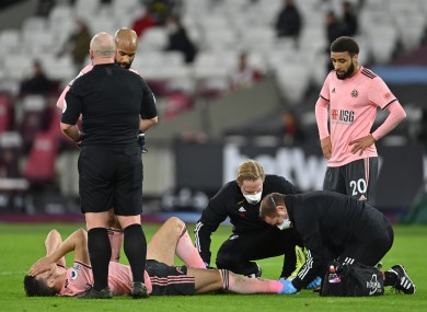 Egan is treated for the injury he sustained against West Ham.