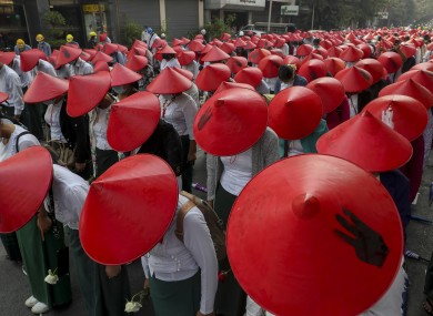 Anti-coup school teachers in their uniform and traditional Myanmar-hats participate in a demonstration in Mandalay, Myanmar