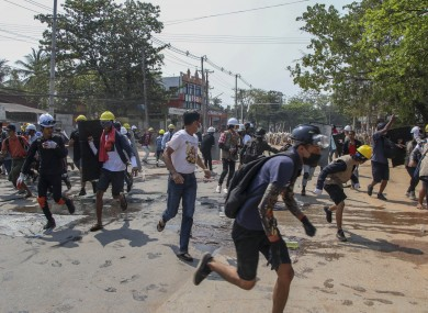 Anti-coup protesters scatter after police fire sound grenades and fire rubber bullets in Yangon, Myanmar.