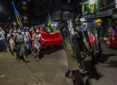 Residents march despite an overnight curfew in an anti-coup night rally in Yangon