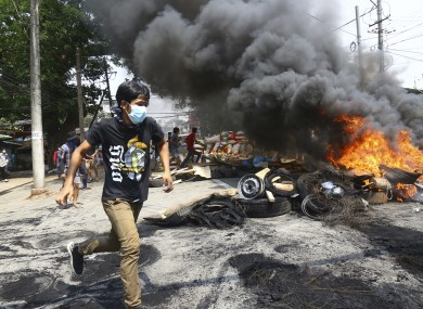 Anti-coup protesters run around their makeshift barricade they burn to make defence line during a demonstration in Yangon, Myanmar