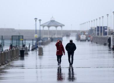 File photo - People walking in heavy rain along Dun Laoghaire Pier
