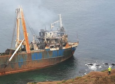 A Fire Fighter surveys the damage on the cliff above the MV Alta.