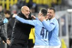 Manchester City manager Pep Guardiola celebrates with goal scorer Phil Foden and Kyle Walker (right).