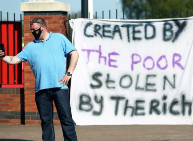 A fan stands outside Old Trafford in response to the news of a proposed Super League.