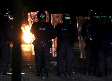 PSNI officers look on after a Loyalist throws a petrol bomb in Belfast last night