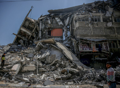 A Palestinian walks past the rubble piled up in Gaza, following the ceasefire agreement.