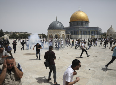 Palestinians run from sound bombs thrown by Israeli police at the Dome of the Rock shrine at al-Aqsa mosque.