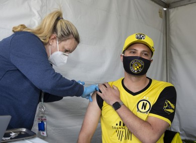 Columbus Crew SC supporter Steven Garver receives his J&J Covid vaccine from a Columbus Public Health nurse.