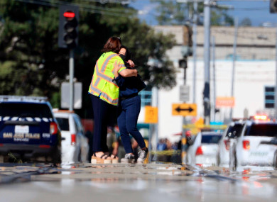 Two people hug on Younger Avenue outside the scene of a shooting in San José.