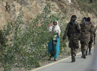 A woman walks past Ethiopian government soldiers by the side of a road north of Mekele, in the Tigray region of northern Ethiopia