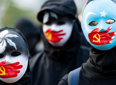 Protestors wear masks symbolising the silencing of the Uyghur people by China.
