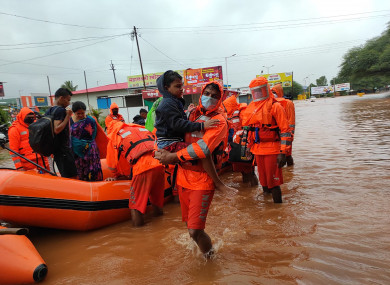 This photograph provided by India's National Disaster Response Force (NDRF) shows NDRF personnel rescuing residents in Chiplun area in the western Indian state of Maharashtra - 24 July