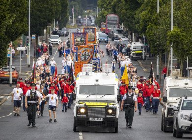 Bandsmen and Orange Order members of No 3 District Loyal Orange Lodge parade pass the nationalist area around Ardoyne shops in Belfast.