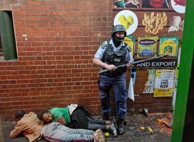 A police officer detains rioters in Johannesburg, South Africa.