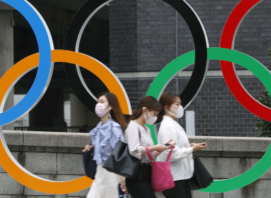 People wearing face masks walk past the Olympics Rings statue in Tokyo