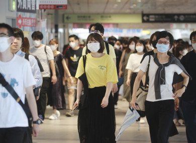 People wearing face masks to protect against the spread of the coronavirus walk at train station in Tokyo.