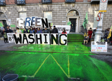 A man sprays the road with green paint as part of a Extinction Rebellion protest over climate change at Fine Gael HQ in Dublin in February 2020.
