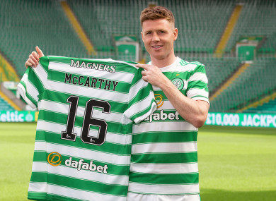 James McCarthy holding up the Hoops shirt with his name and number on the back.