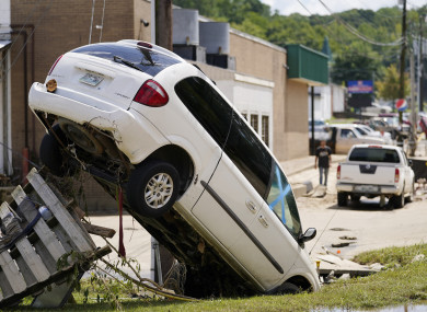A car leans against a utility pole after being upended by floods.