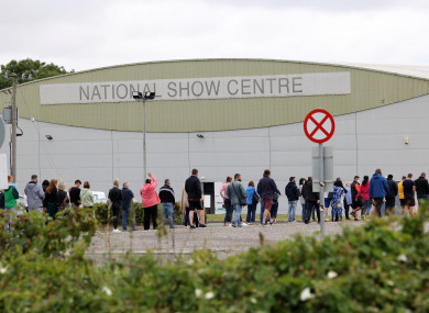 People queue outside a walk-in vaccination centre at the National Show Centre in Swords, Dublin this morning.