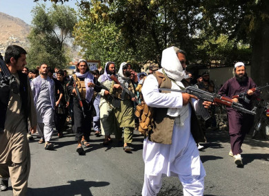 Taliban soldiers walk towards Afghans during a protest in Kabul
