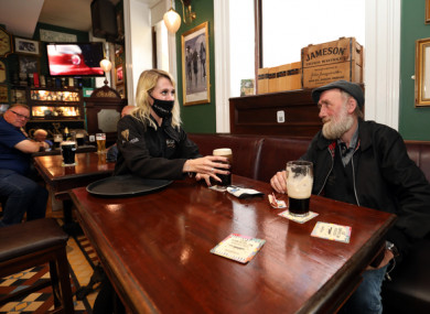 Customer Jimmy Nooks getting a pint of Guinness from bar staff Becky Roche who in PJ Slattery's pub Dublin.