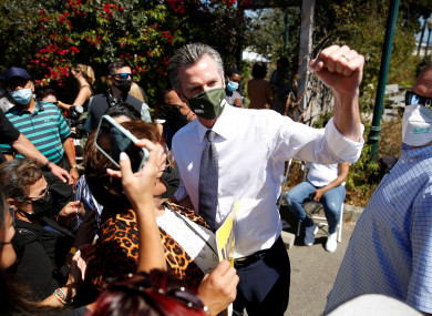 California Governor Gavin Newsom takes photos with supporters in Oakland.