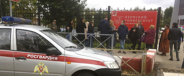 People stand behind the fence near the Perm State University with the a Posguardia.