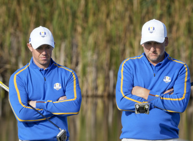 Team Europe's Rory McIlroy and Ian Poulter wait to putt.